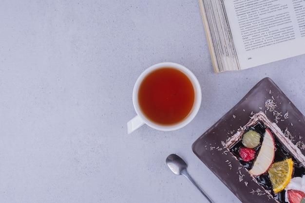 Uma fatia de bolo de chocolate com uma xícara de chá, vista de cima