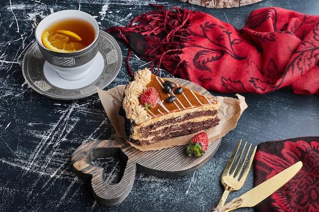 Uma fatia de bolo de chocolate e caramelo com uma xícara de chá.