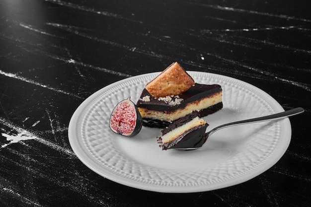 Uma fatia de bolo de chocolate em um prato branco com frutas e biscoitos.