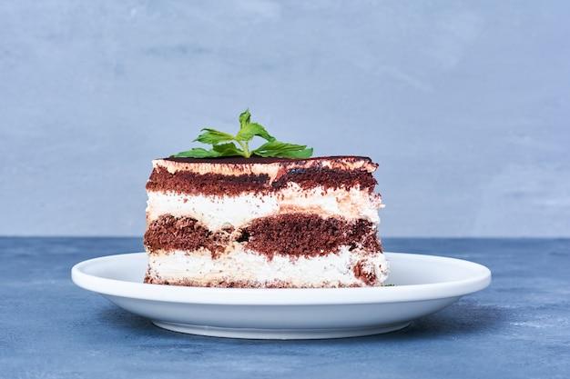 Uma fatia de bolo de chocolate em um prato branco.