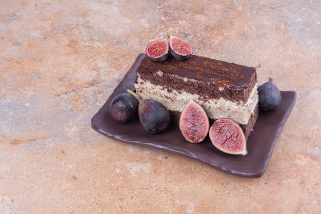 Uma fatia de bolo de chocolate em uma travessa preta com figos.