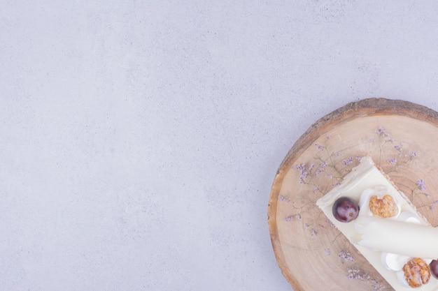 Uma fatia de bolo de coco com uva e noz em uma placa de madeira