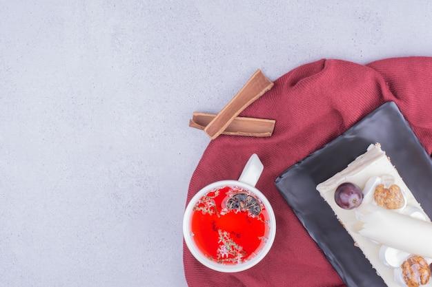 Uma fatia de bolo de coco com uva e nozes servida com uma xícara de chá de ervas