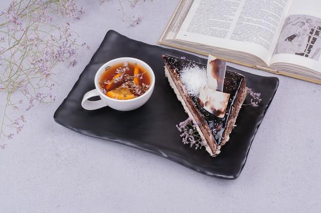 Uma fatia de bolo de ganache de chocolate com uma xícara de chá de ervas.