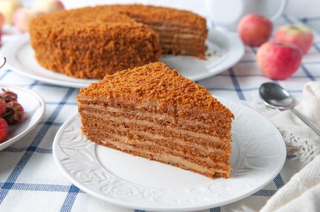 Uma fatia de bolo de mel caseiro multicamadas cor de laranja em um prato branco closeup testura perto estão frutas, maçãs e bolo toalha de mesa em estilo rústico