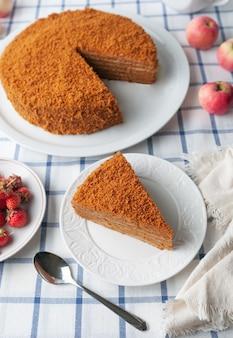Uma fatia de bolo de mel caseiro multicamadas. cor laranja. num prato branco. vista de cima. testura. perto estão frutas, maçãs, bolo, colher. toalha de mesa em estilo rústico.