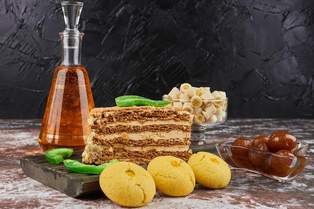 Uma fatia de bolo de mel com biscoitos de manteiga e uma garrafa de bebida.
