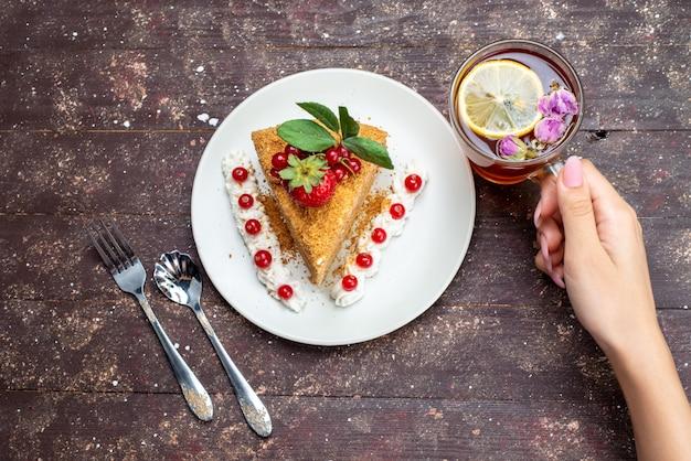 Uma fatia de bolo de mel com cranberries dentro de um prato branco, juntamente com um chá no fundo escuro.