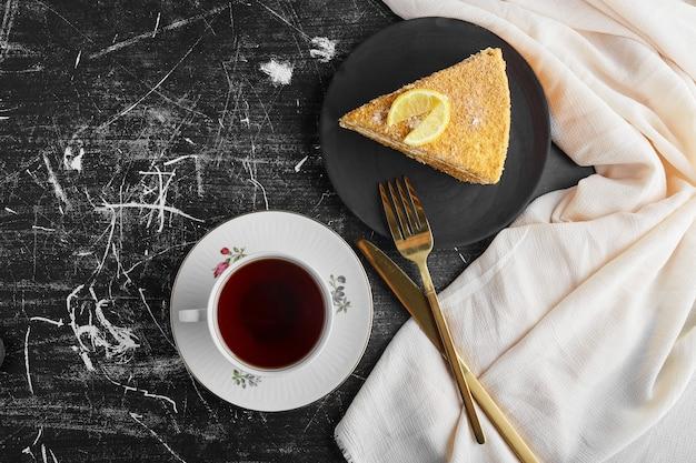 Uma fatia de bolo de mel com limão com uma xícara de chá.