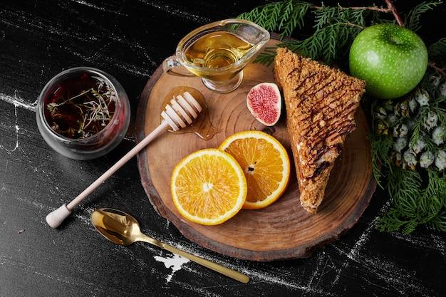 Uma fatia de bolo de mel com rodelas de laranja e chá de ervas.
