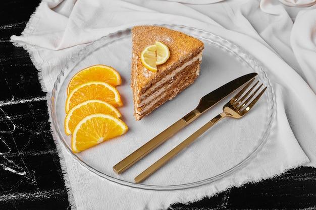 Uma fatia de bolo de mel com rodelas de laranja.