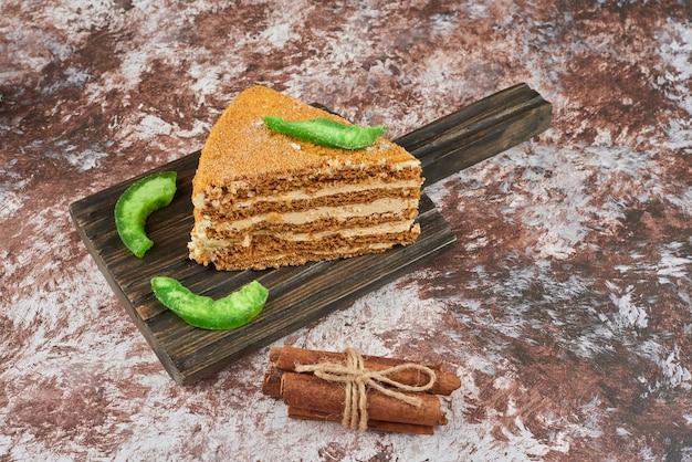 Uma fatia de bolo de mel em uma bandeja de madeira.