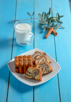 Uma fatia de bolo de mel tradicional com canela em pó e uma xícara de chá.