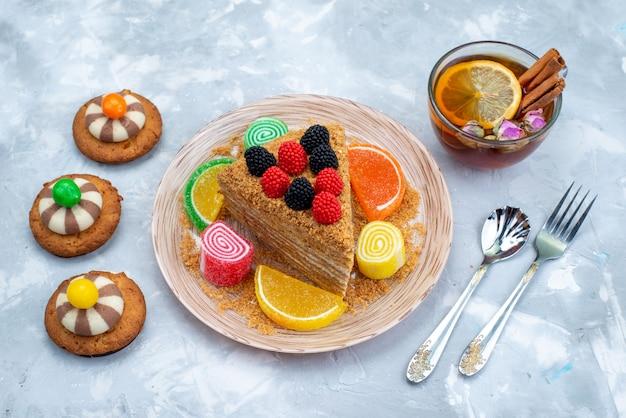 Uma fatia de bolo de mel vista de cima dentro do prato com biscoitos doces e chá na mesa azul.