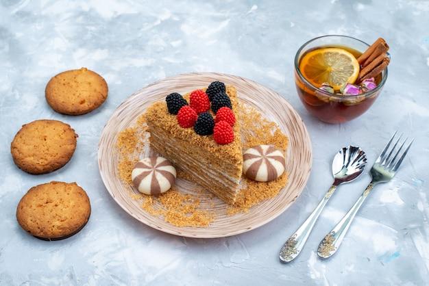 Uma fatia de bolo de mel vista de cima dentro do prato com biscoitos doces e chá no fundo azul.