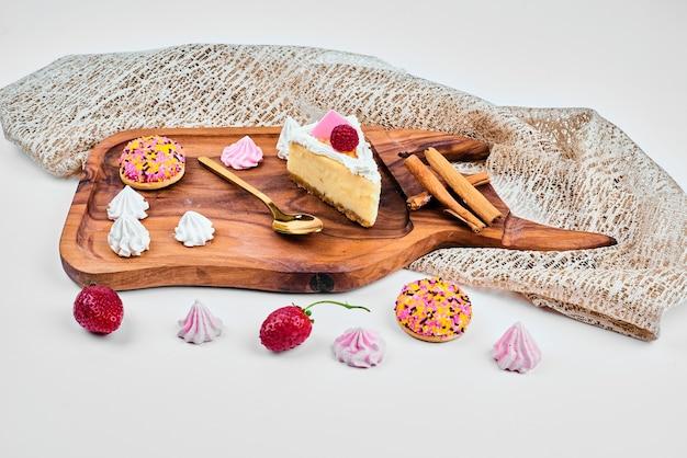 Uma fatia de bolo de queijo em uma placa de madeira.