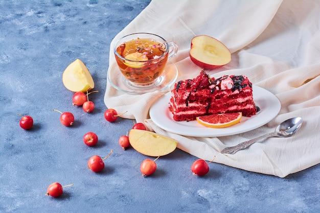 Uma fatia de bolo de veludo vermelho em um prato branco com chá.