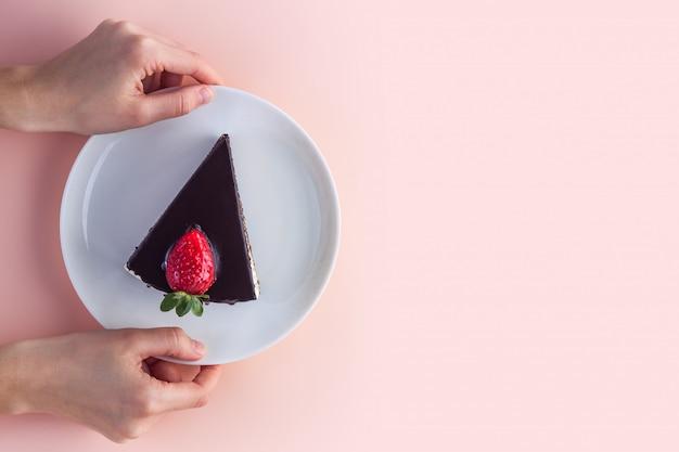 Uma fatia de bolo doce de morango com gotas de cobertura de chocolate em um prato branco nas mãos de rosa