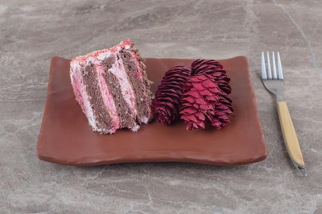 Uma fatia de bolo e pinhas vermelhas em uma travessa ao lado de um garfo no mármore