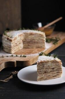 Uma fatia de bolo em um prato. bolo de panqueca com creme de leite, decorado com açúcar de confeiteiro e raminhos de tomilho. sobremesa em uma grande placa de madeira. prato em uma velha mesa de cozinha rústica.