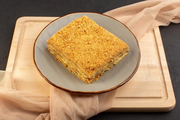 Uma fatia de bolo gostosa e assada dentro de um prato na mesa de madeira e um bolo escuro de biscoito com açúcar