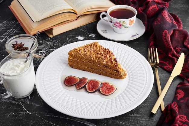 Uma fatia de bolo medovic com figos, coalhada e chá.