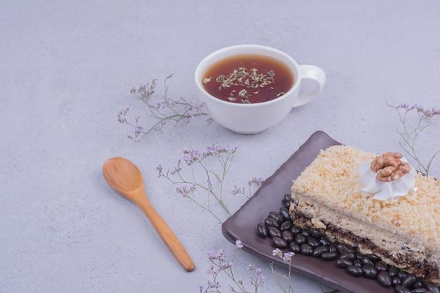 Uma fatia de bolo medovic com grãos de chocolate em uma travessa preta com uma xícara de chá