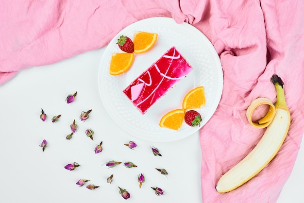 Uma fatia de bolo rosa com frutas, vista superior.