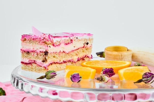 Uma fatia de bolo rosa com frutas.