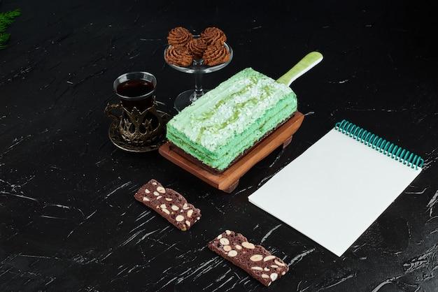 Uma fatia de bolo verde com um livro de receitas.