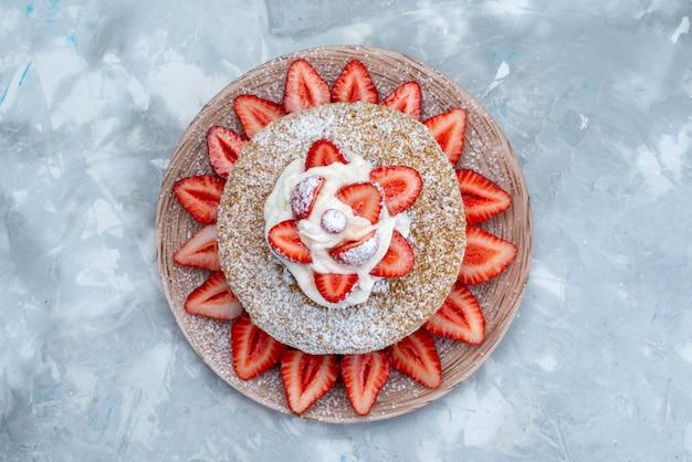 Uma fatia de bolo vista de cima com creme e morangos vermelhos frescos dentro do prato no fundo cinza-azulado