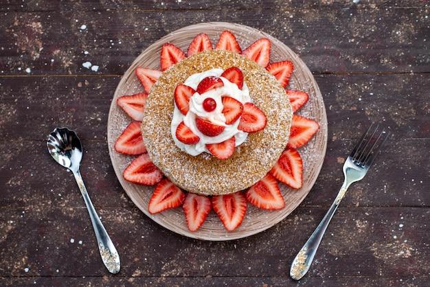 Uma fatia de bolo vista de cima com creme e morangos vermelhos frescos dentro do prato no fundo escuro