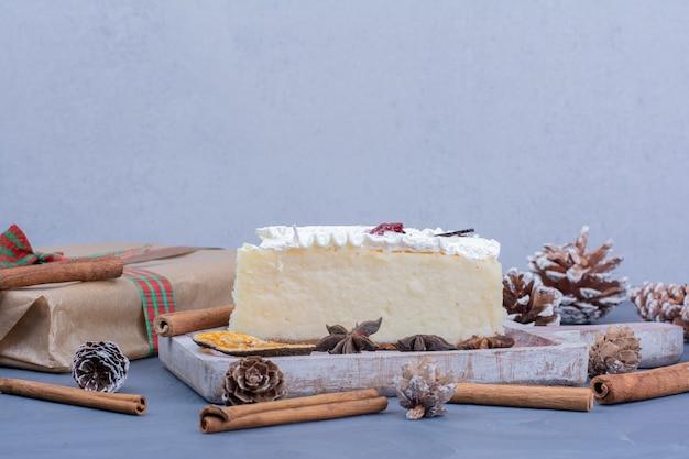 Uma fatia de cheesecake com anis e canela em travessa rústica.