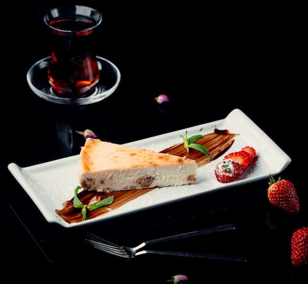 Uma fatia de cheesecake com calda de chocolate, menta, morangos e um copo de chá preto.