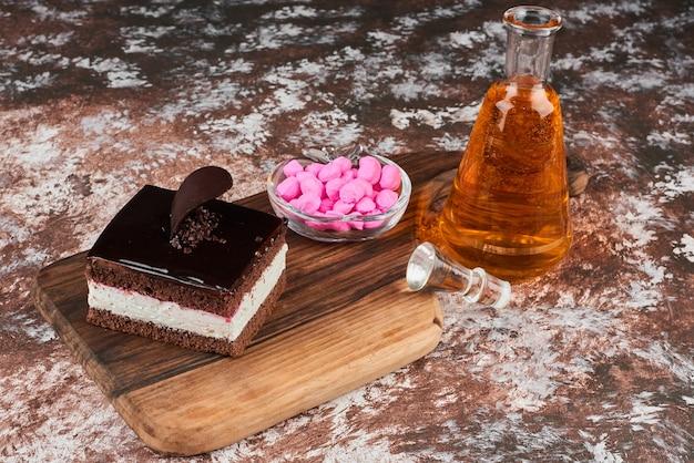 Uma fatia de cheesecake de chocolate com uma garrafa de bebida e doces.