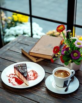 Uma fatia de cheesecake de framboesa servida com café expresso