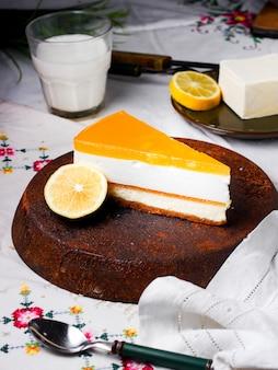 Uma fatia de cheesecake de limão, guarnecida com uma fatia de limão
