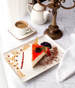 Uma fatia de cheesecake de morango, guarnecida com pedaços de morango e chocolate