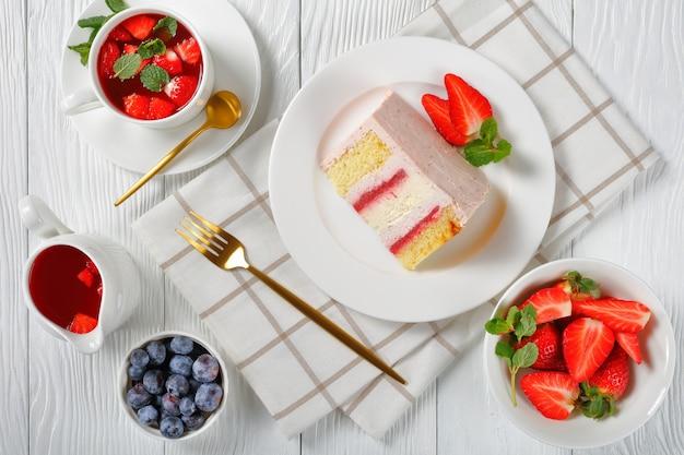 Uma fatia de cheesecake de morango rosa servido com frutas frescas e limonada de morango em uma mesa de madeira