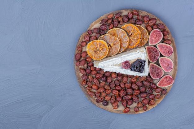 Uma fatia de cheesecake em uma travessa de frutas com figos, fatias de laranja e quadris