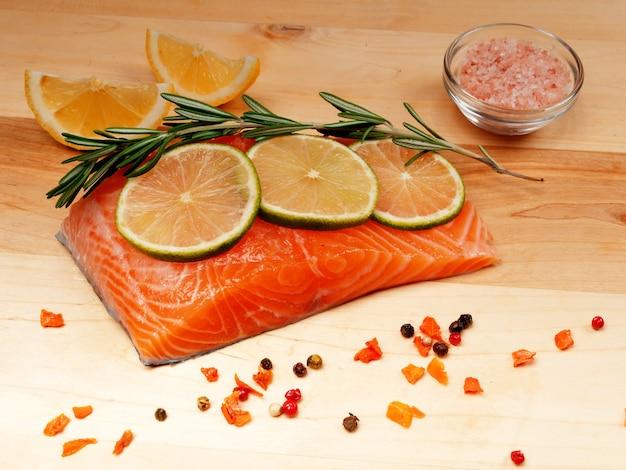 Uma fatia de filé de salmão cru fresco vermelho com limão e alecrim e especiarias próximas. deitar sobre uma tábua de madeira. conceito de comida saudável