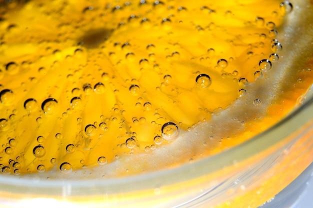 Uma fatia de laranja coberta de bolhas encontra-se em um copo de água com gás. fechar-se.