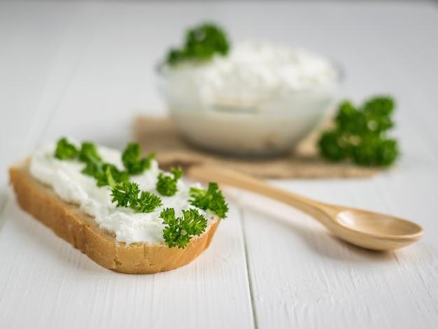 Uma fatia de pão fresco manchada com creme de queijo cottage com salsa em cima da mesa.