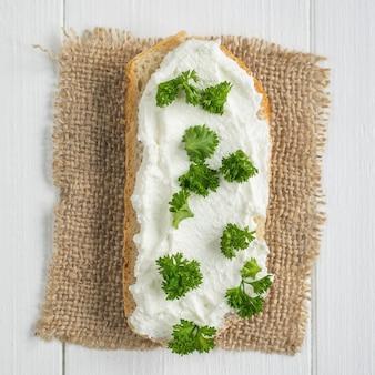 Uma fatia de pão fresco manchada com creme de queijo cottage com vista superior de salsa.
