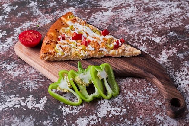 Uma fatia de pizza com tomate e pimenta no mármore.