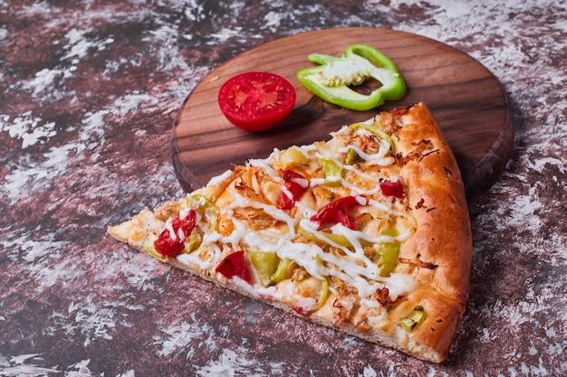 Uma fatia de pizza com tomate e pimenta.