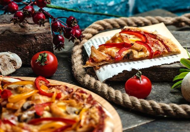 Uma fatia de pizza e tomate em cima da mesa