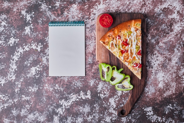 Uma fatia de pizza em uma placa de madeira com um livro de receitas à parte no mármore.