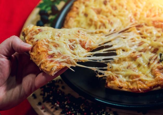 Uma fatia de pizza na mão. um restaurante.