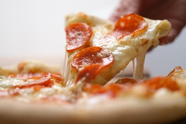 Uma fatia de pizza quente fresca suculenta é retirada da caixa. conceito de entrega de pizza